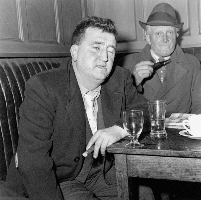 "Irish playwright Brendan Behan, whose plays ""The Quare Fellow"" and ""The Hostage"" were enthusiastically received in London's West End, enjoys a drink and a chat with his friend Michael Collins in Tom Moore's Bar in Dublin, Ireland."
